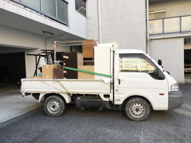 不用品を載せた平ボディの軽トラック