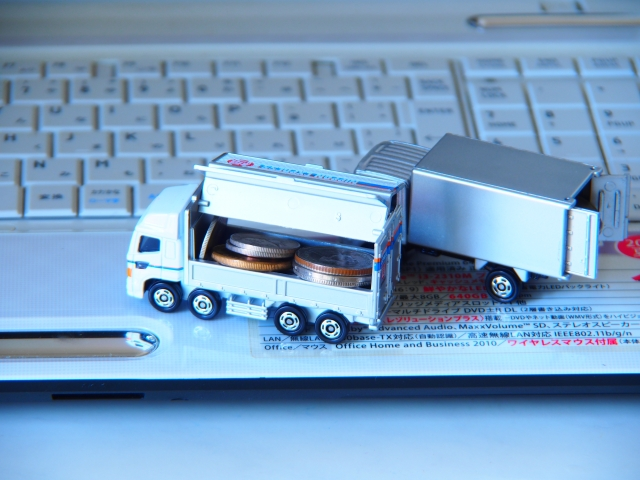 パソコンの上に小銭を積んだおもちゃのトラック