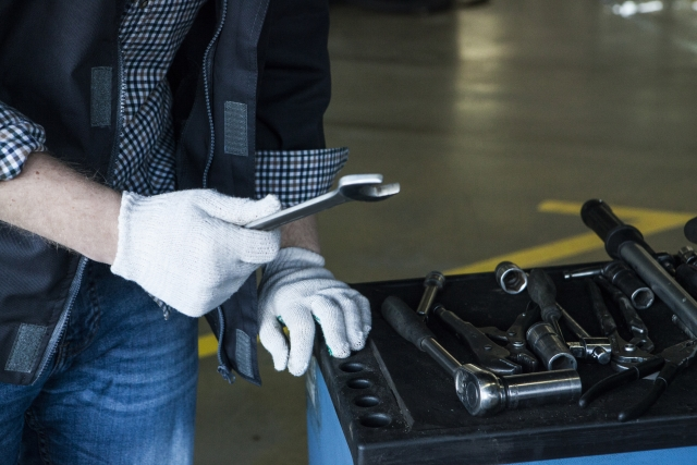 工具を選ぶ自動車整備士の手元