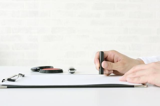契約書に捺印する人物の手