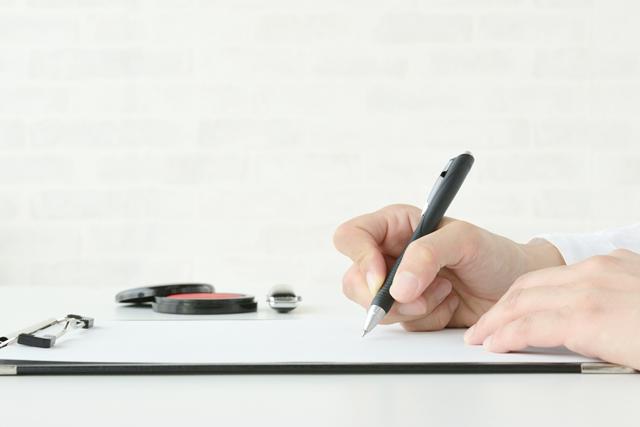 契約書にサインする人物の手