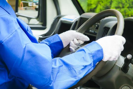 運転をする青色の作業服の人