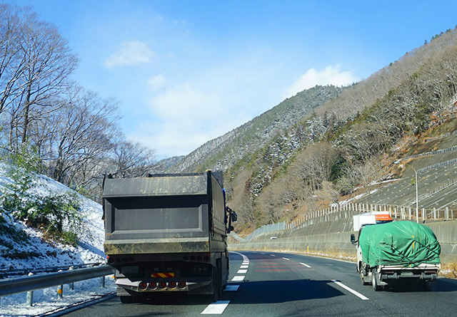 沿道に雪が残る道を走るトラック