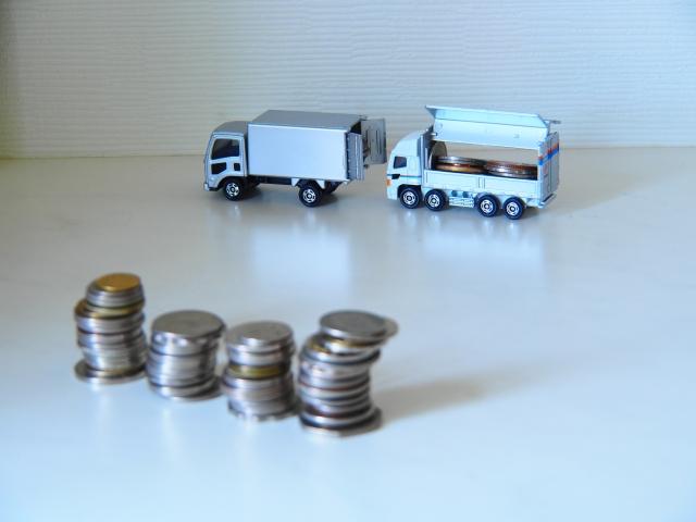 ミニチュアのトラックと積み重ねられた小銭